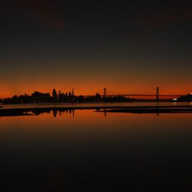View over the City of San Francisco as the sun has set with the Bay Bridge and Oakland harbor in the foreground
