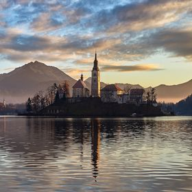 The church on Bled Island shimmers with golden light as the sun rises in Lake Bled, Slovenia.   Photographing a morning in this spot, watching ni...
