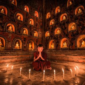Novice monk praying with a candle inside a temple by Shwe Yan Pyay Monastery in Nyaung Shwe, Myanmar.  www.drewhopperphotography.com  For image ...
