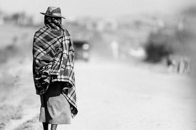 Old lady walking along the roadside