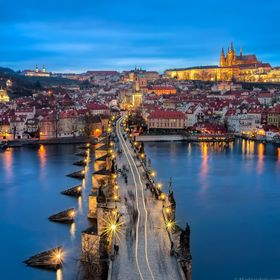 A city vehicle makes it way across Charles Bridge through the crowds of people as night descends upon Prague. In the distance, the largest castle...