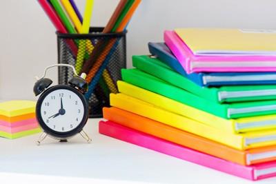 Black alarm clock and multi colored books in stack