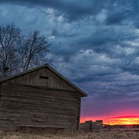The springtime sun sets behind the barns and fields of the Northern Finland. The clouds are especially dramatic.  | TheTravelPictures.com |
