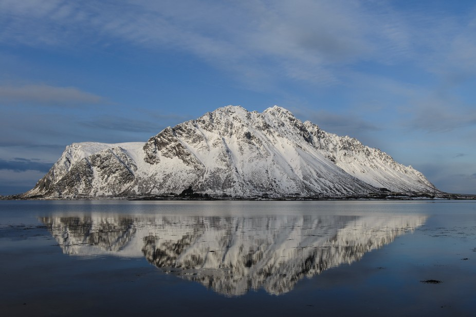 Flat calm sea in this bay near Svolvær in the Lofotens in February.  The reflection deepened to this emerald blue as the sky cleared.