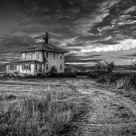 This is a B&W photograph of the pink house near Plum Island, MA. Here is a link to the back story of the Pink House: http://www.nytimes.com/2...