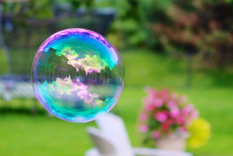 A close up shot of a beautiful soap bubble that I made in my backyard with the reflection of my h...