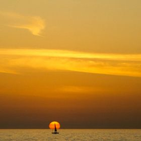 Driving in the busy streets of Tel Aviv watching the sun set over the Medeterranean Sea and a sailboat tacking steadily towards the place the sun...