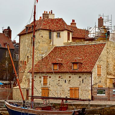 Honfleur was built essentially for commerce. Its harbor sits in a great location, tucked away on the southern side of the Seine's estuary. During the Hundred Years War, the French king had this strategic spot fortified, but that didn't stop the English taking over for several decades.    There are all types of boats here including this small sailboat.   D810 with 24-120 f/4G ED VR lens at 98 mm, f/8, 1/160 Auto ISO 90 manual mode hand held. Processed in Capture NX-D and PSCS6 Extended using Picture Postcard Workflow.