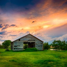 An old grainery near my hometown. Storm clouds moved through the area at sunset which gave the clouds an orange glow. There is a little pond behi...