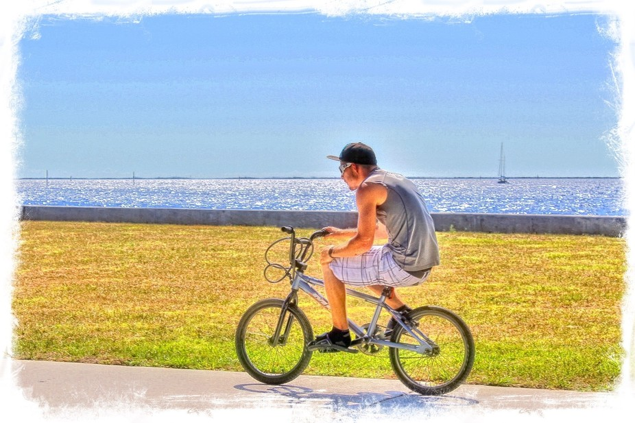 Boy riding low on a bicycle along the riverfront at Gilchrist Park in Punta Gorda, Florida.  Late...