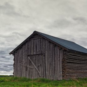 An old barn house locked up in the middle of the fields of the Northern Finland. The clouds of the summer are gathering upon it and predicting so...