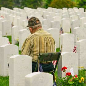 A heartfelt moment as an elderly man sits by the grave of a deceased vet.