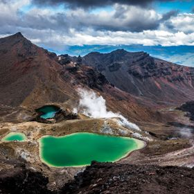The beautiful emerald lakes in the National Park of Tongariro in New Zealand. Holes in the ground from where white smoke slowly seeps out...