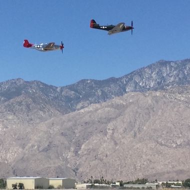 A Palm Springs Air Museum P-51 Mustang and a P-63A King Cobra, over the Palm Springs Airport during the Memorial Day celebration at the PSAM.