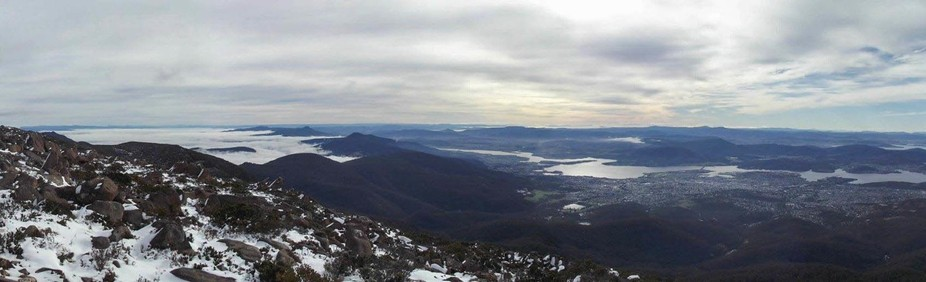 a shot from the top of Mt Wellington overlooking the city of Hobart and fog rolling in from the west