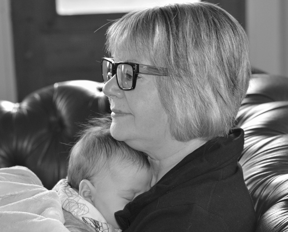 Black and white photo of a grandmother holding a sleeping baby.