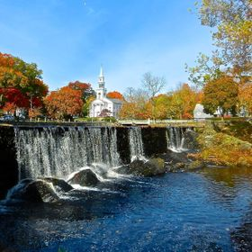 This duck pond is behind the Milford Town Hall in Connecticut. The waterfall and pond pictured here with the trees in autumn colors and church ag...