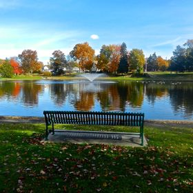 New England Park with pond, fountain, a bench in the foreground and autumn colors in the background. Trees reflection in the water.