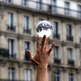 Street performer holding his glass ball reflecting his surroundings mid-show.