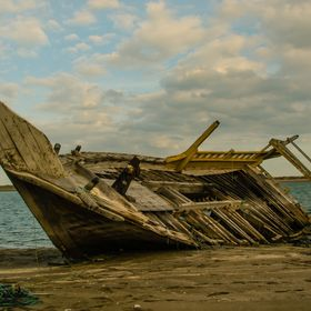 This once was a beautiful arabian boat, now abandoned and lying on its side in old town of Fujairah.