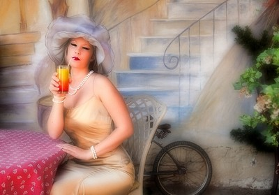 Blonde sipping on a cocktail in a French Riveira Style Cafe