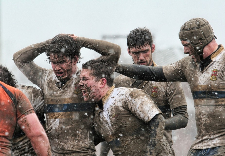 Rugby players regrouping during a snowy muddy game