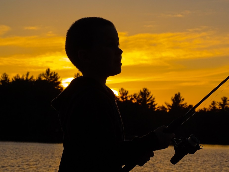Young boy trying to his luck at fishing as the sun sets Muskoka, Ontario