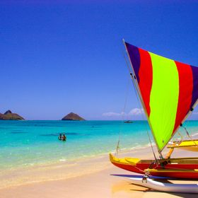 While relaxing on Lanikai Beach, a family arrived and prepared to put their colorful trimaran into the water. The bold colors of the boat really ...