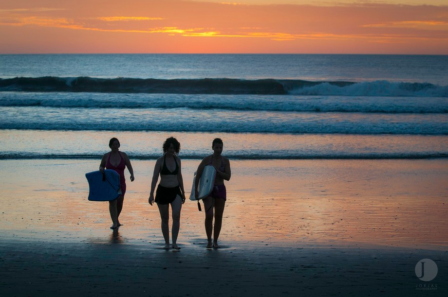 Three women taking in the last bit of high tide for boogie boarding on the Costa Rican shores