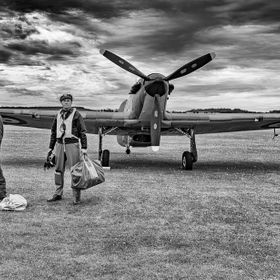 A pilot stands in front of a Hurricane at Duxford Flying Legends Show.