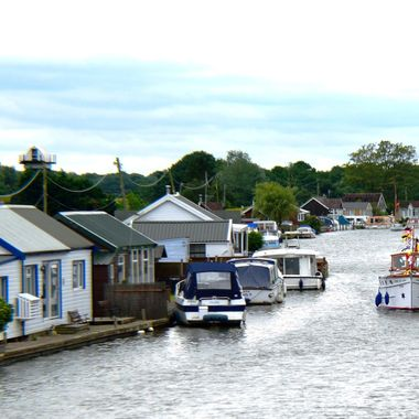 View along the river at Potter Heigham on the Norfolk Broads in the UK.