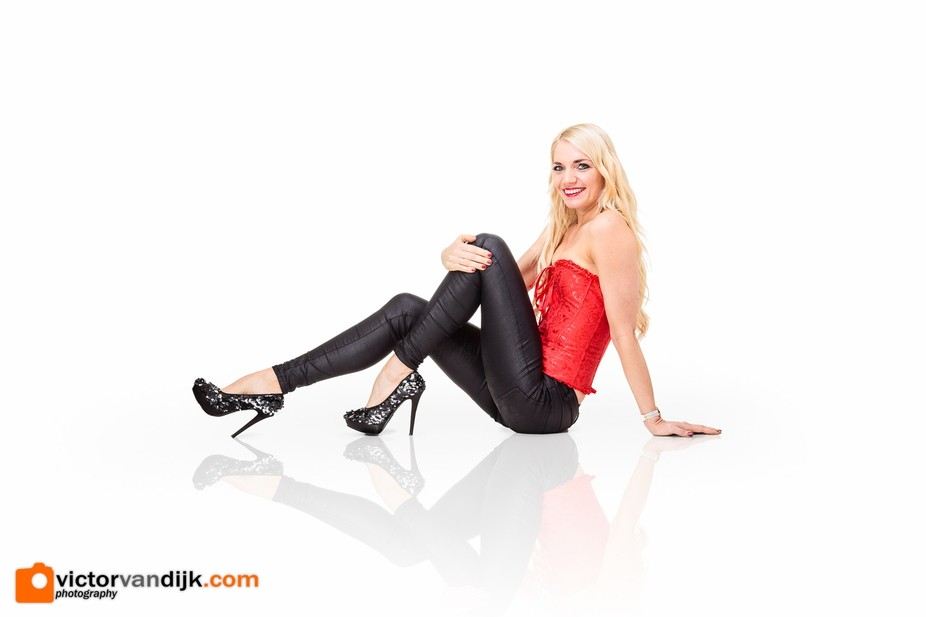 Blonde model with high heels, black legging and red corset. What more could you want in your stud...