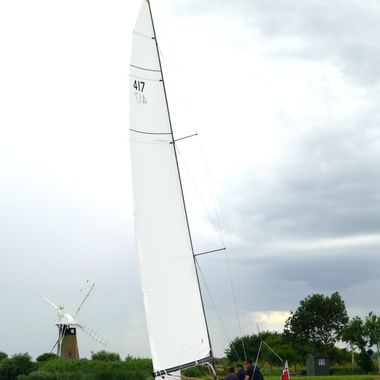Yacht sailing on the river near St Benet's Mill in Norfolk, UK.