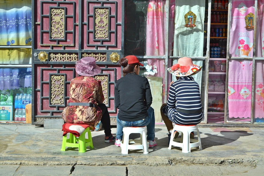 Three Tibetan women sitting on stools in front of their shops chatting and watching people. Pictu...