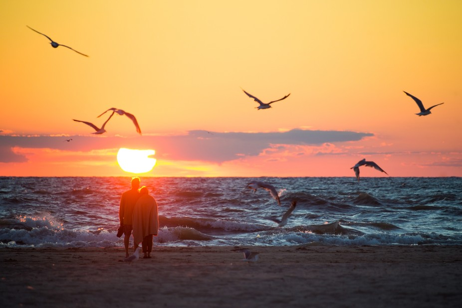 A couple on North Beach watching the sunset over Lake Michigan on a windy day in South Haven, Mic...