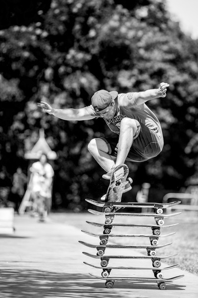 Sporty guy with a hat is jumping nicely over stacked skate boards