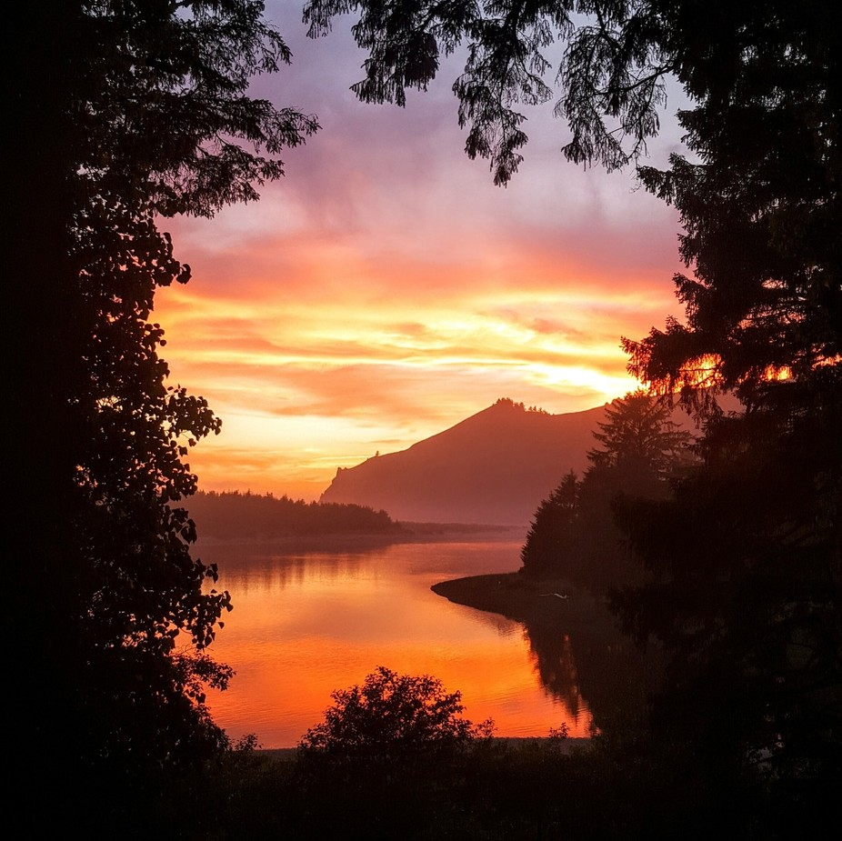Sun going down over the Pacific Ocean behind Cascade Head throwing it's colors over the ...