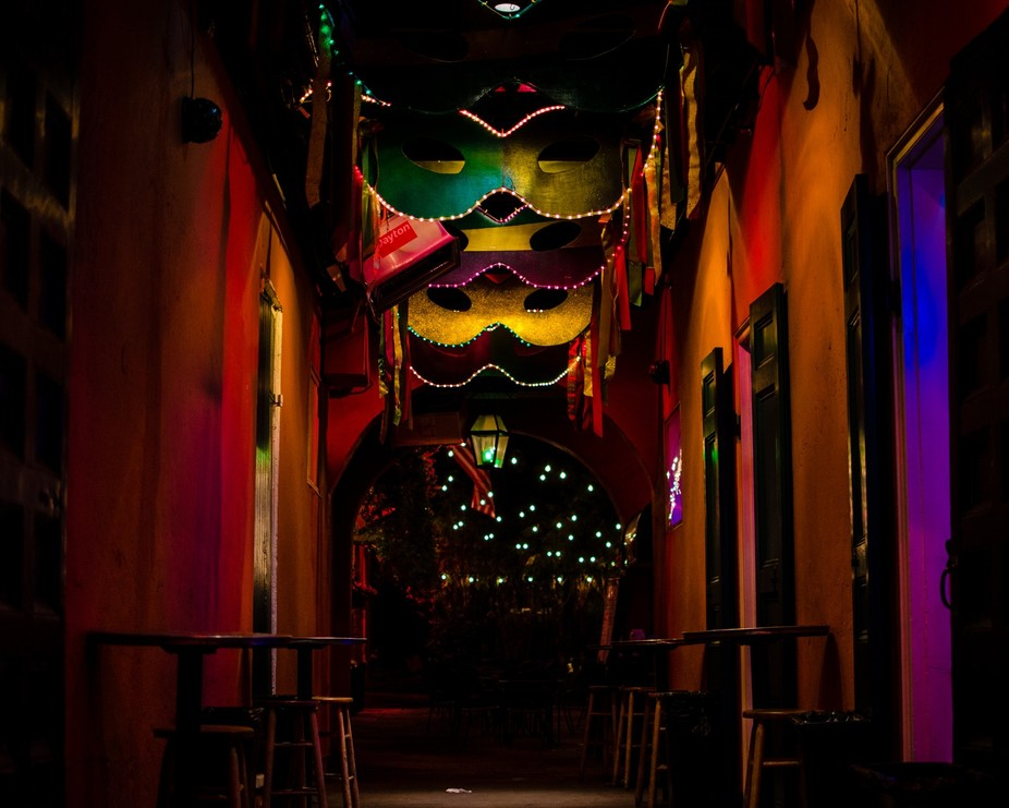 A bar in an alley off Bourbon Street in New Orleans decorated with hanging masks.
