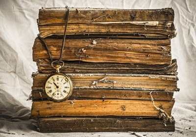 Pile of old dusty books with broken pocket watch on white cloth.