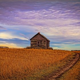 An abandoned farm house sits alone in a prairie field