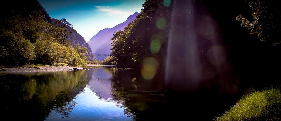 On the Milford track , morning light cats across the river as morning mist adds colour to the mou...