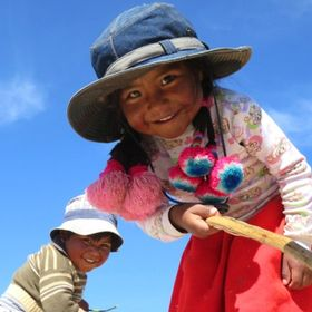 Two brothers, two charming Uros' children  playing whilst posing for the photo. Photo taken at Titicaca Lake, Peru.