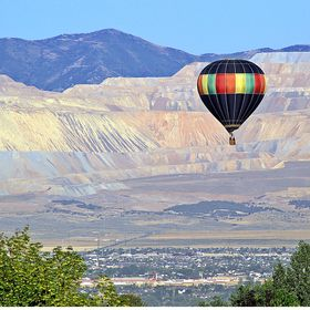 A hot air balloon soaring over the south end of the Salt Lake Valley of Utah.  The Bingham Copper Mine can be seen in the background.