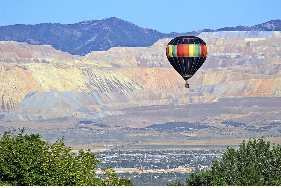 A hot air balloon soaring over the south end of the Salt Lake Valley of Utah.  The Bingham Copper...