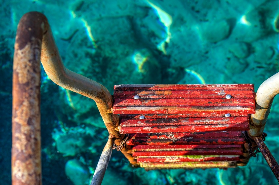 Rusty Ladder leading into turquoise waters
