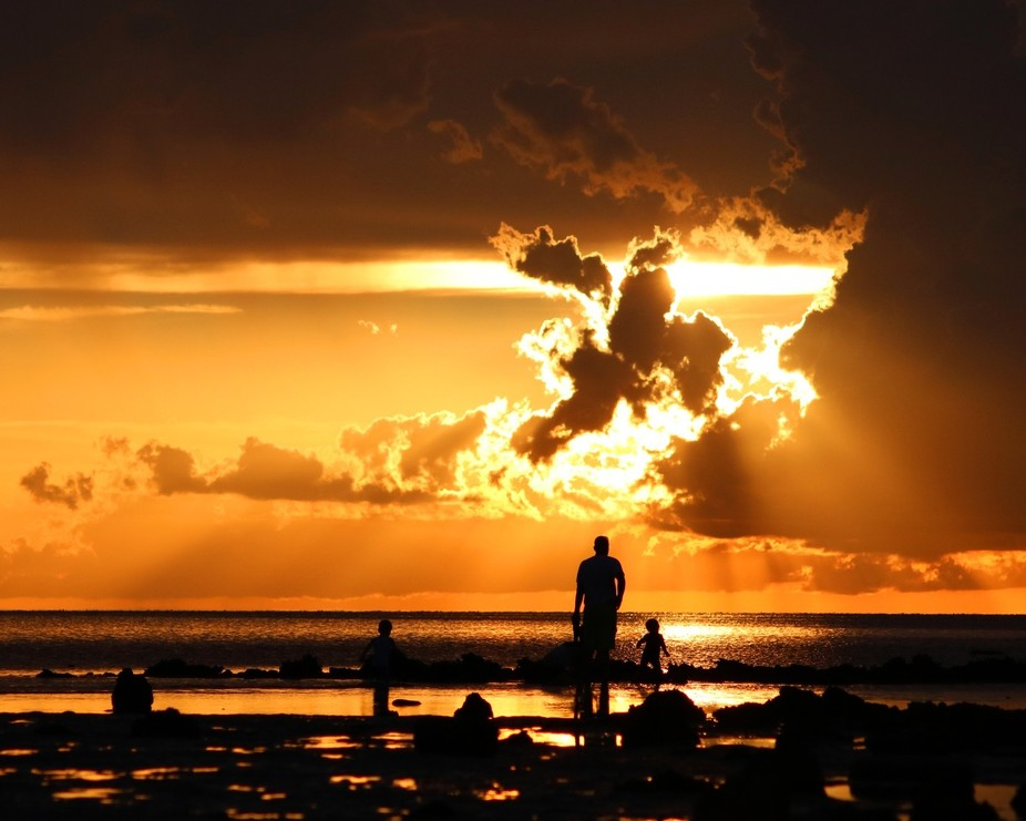 A father with with his children out playing on the rocks at sunset taken at Pine Island beach Flo...