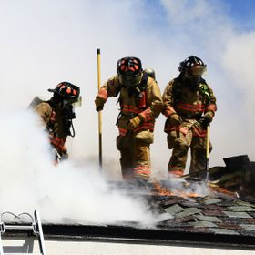 Irving Firefighters working the roof of a single story strip shopping center fire. Irving, Dallas County, Texas, USA. (Approved for public releas...
