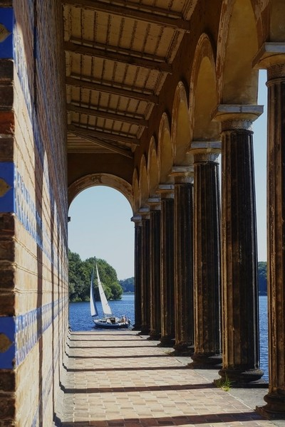 Sail boat passing church colonnades