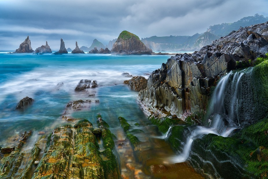 The scene at high tide at Playa de Gueirua on the northern coast of Spain in the Asturias provinc...