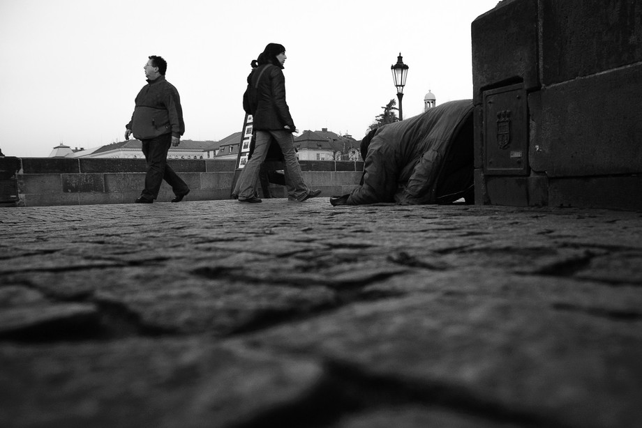 The prostrate man and the church bell tower align along the right third. This image was captured ...